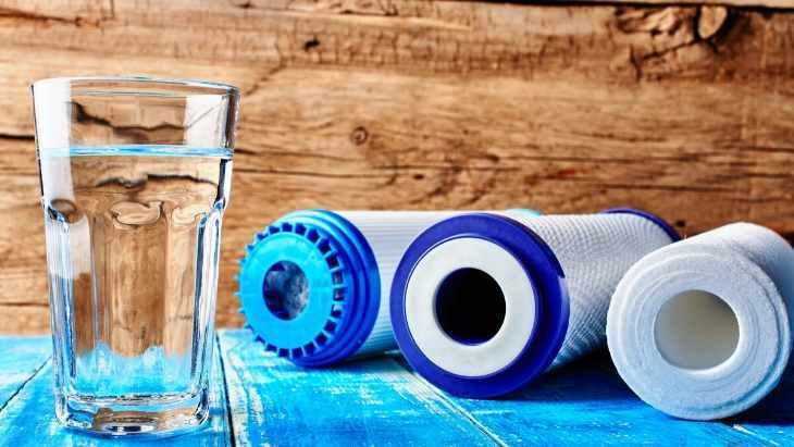 glass of reverse osmosis water and three reverse osmosis filters