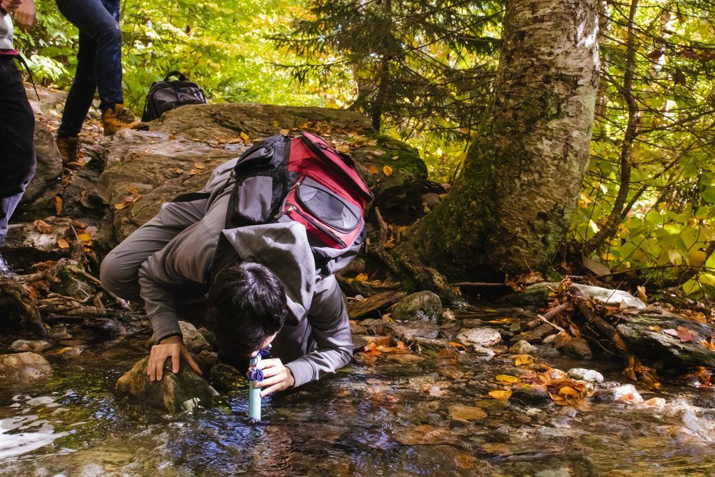 A young man using a water filter to drink water from a mountain stream.