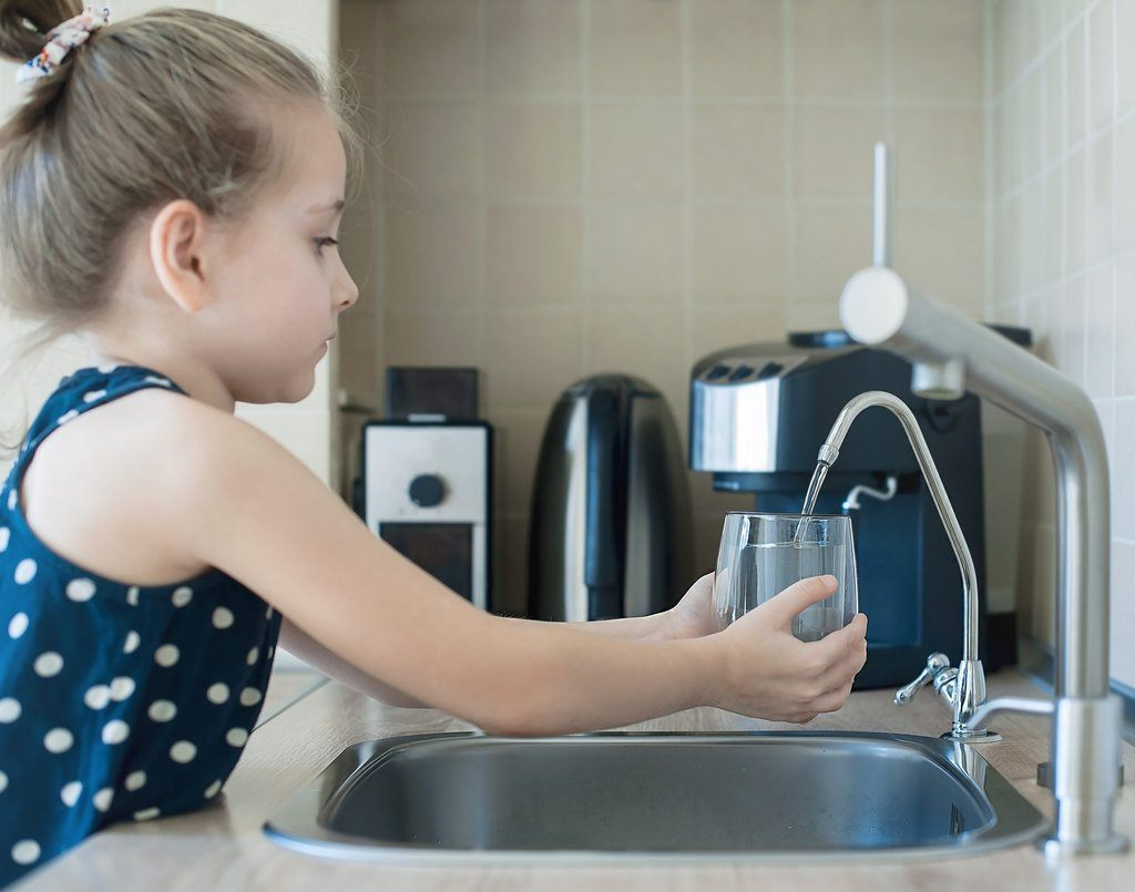 Girl drinking a glass of reverse osmosis filtered water